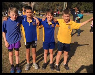 4 boys at district carnival arms around shoulders